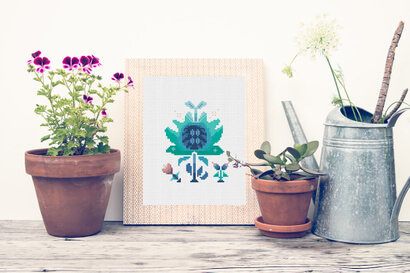 Colorful modern winter flowers cross stitch pattern in frame