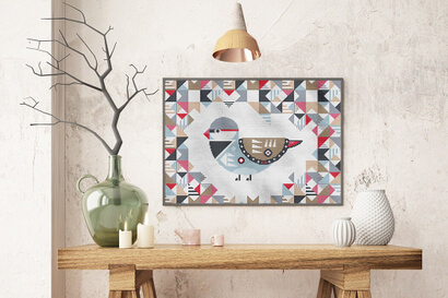 Geometric Birds: diamond firetail cross stitch pattern in large frame over rustic table