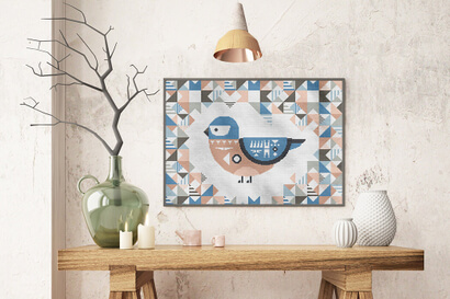 Geometric Birds: eastern bluebird cross stitch pattern in large frame above table